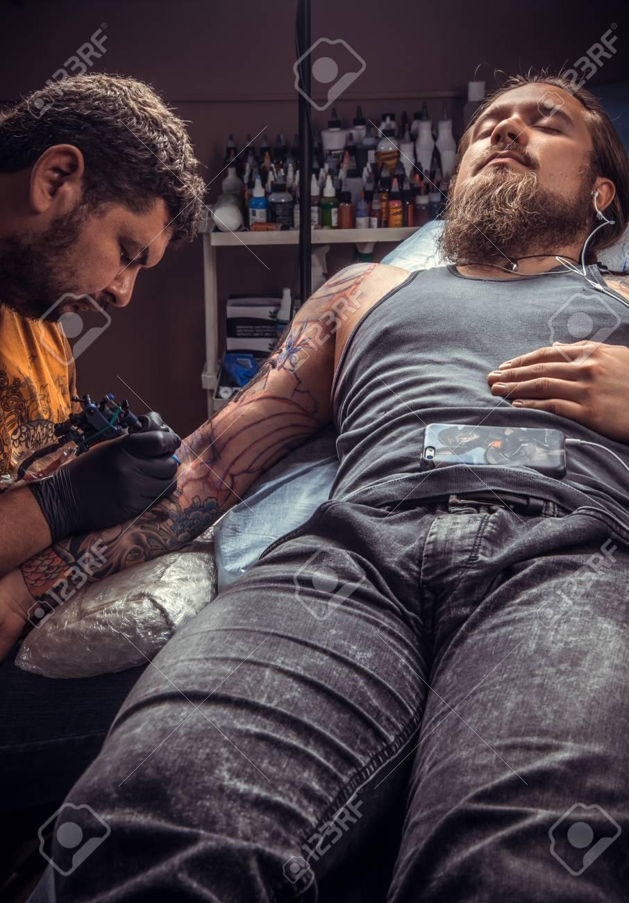 16bc52181 Professional tattooer makes tattoo in tatoo salon./Tattoo artist at work in tattoo  parlor