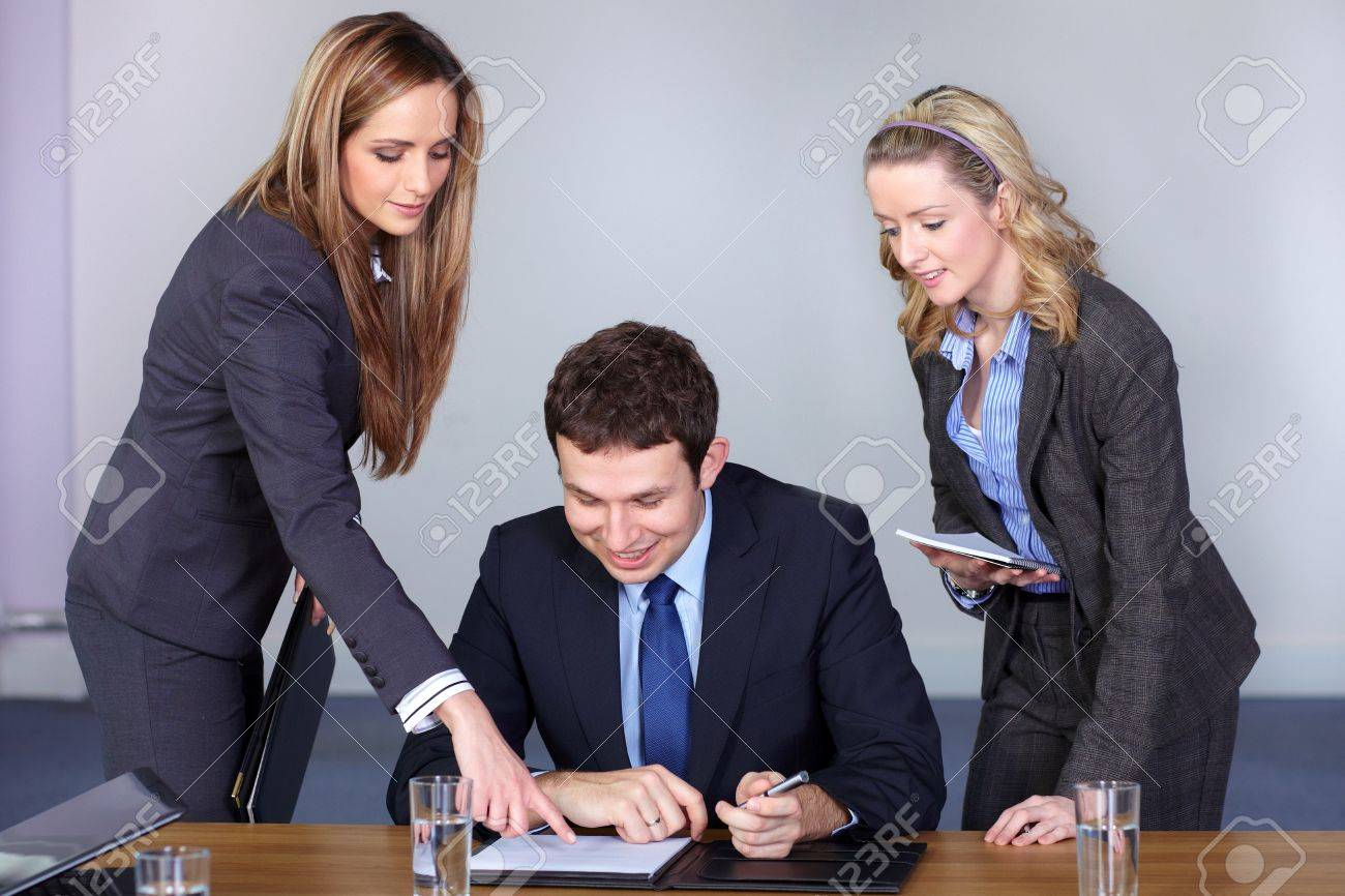 Young businessman and his two attractive female advisors, point something at his paperwork Stock Photo - 11274323