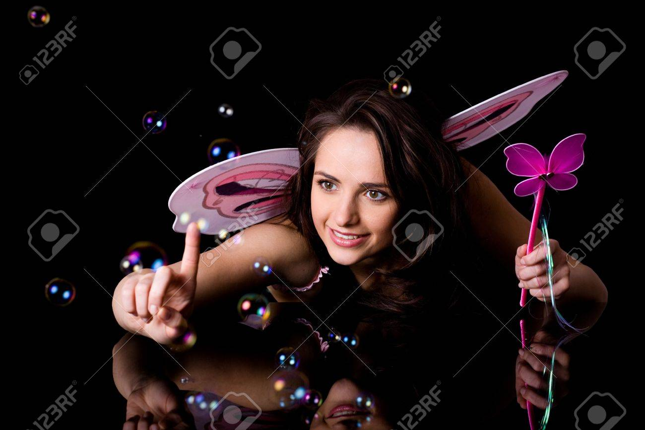 fairy with pink wings and magic wand trying to catch bubbles, studio shoot isolated on black Stock Photo - 11617425