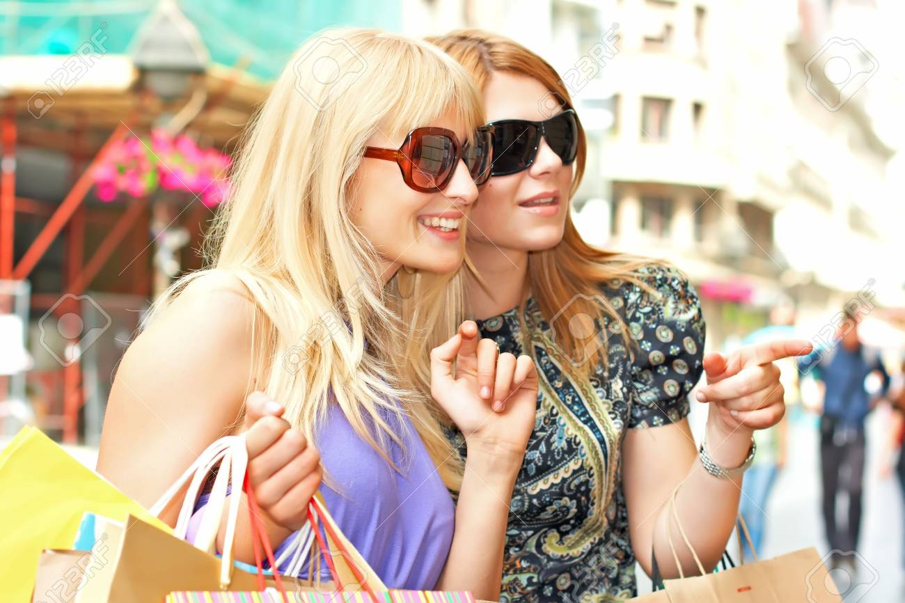 Two shopping woman looking awey with  bags in city environment. Stock Photo - 4897574