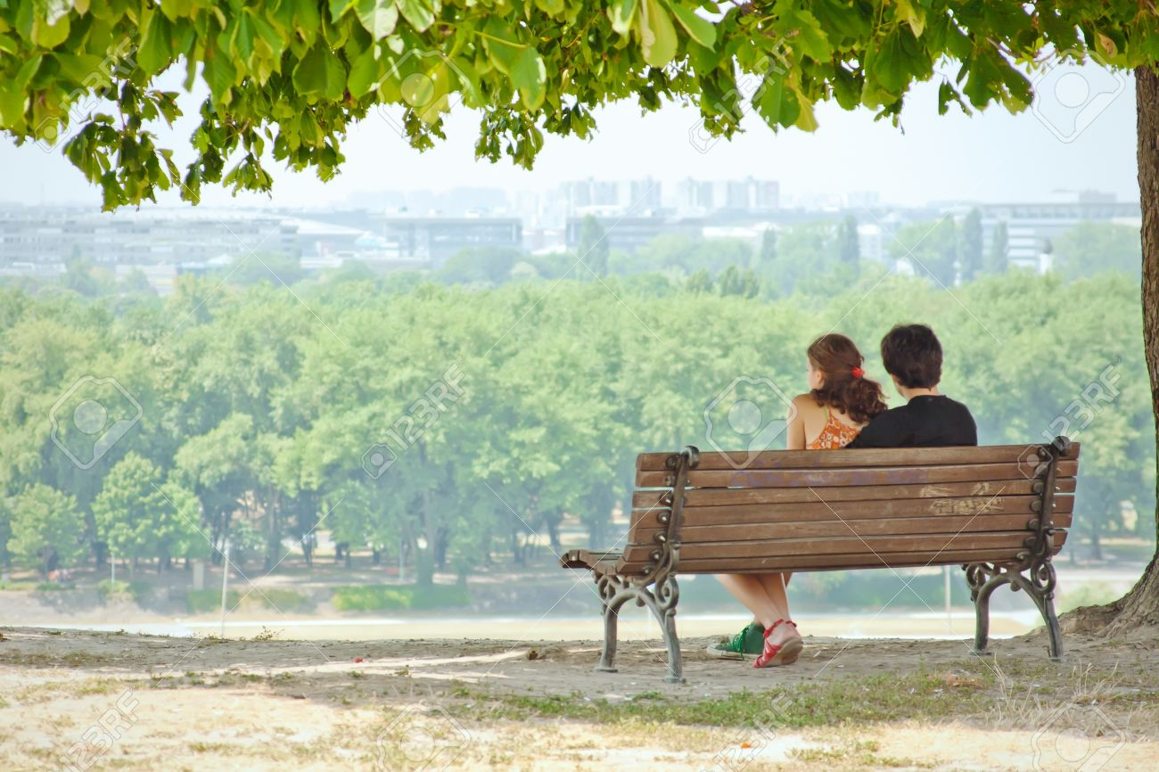 Couple In Love Sitting On A Park Bench And Enjoy The View