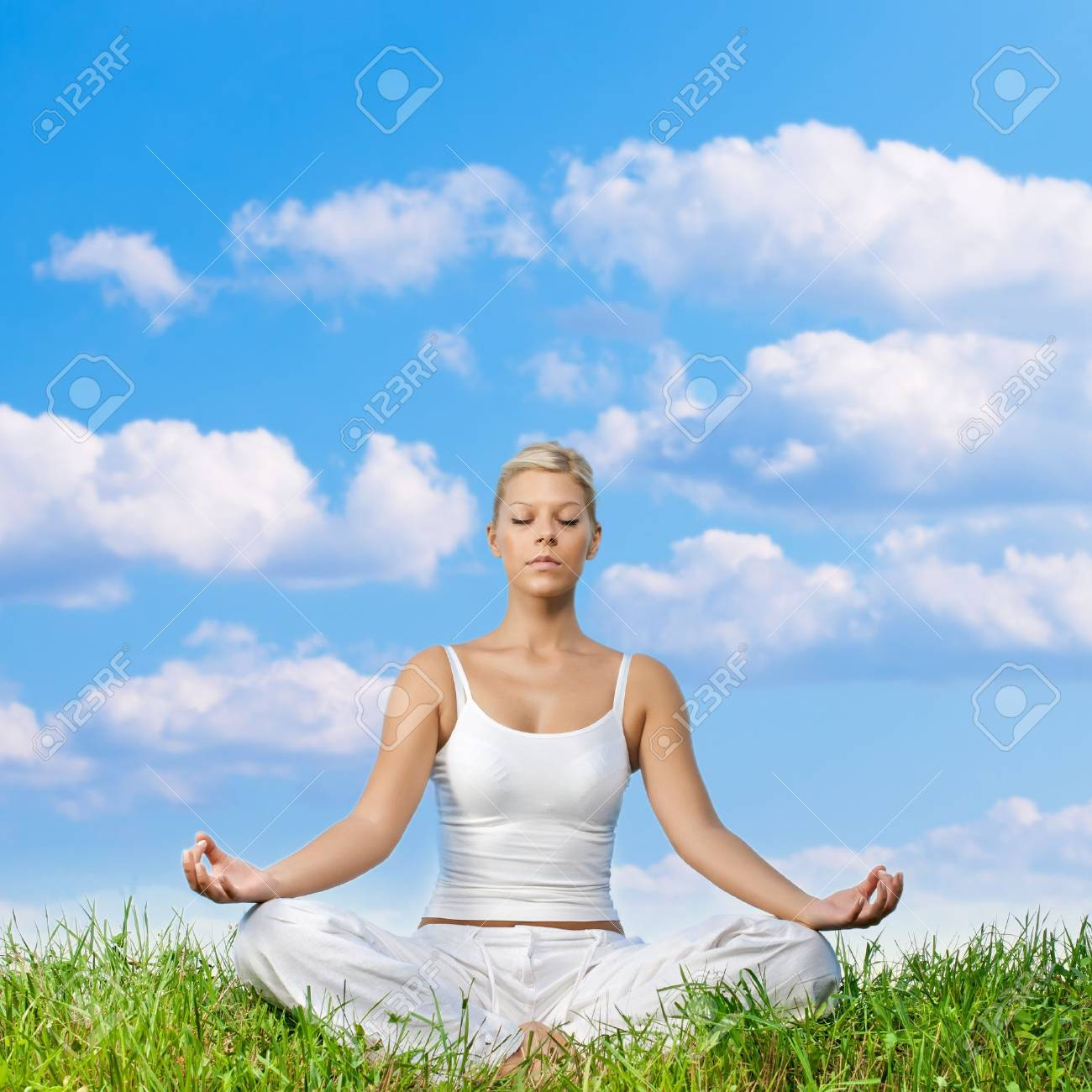 Young woman meditating on green grass with copyspace. Stock Photo - 10411280