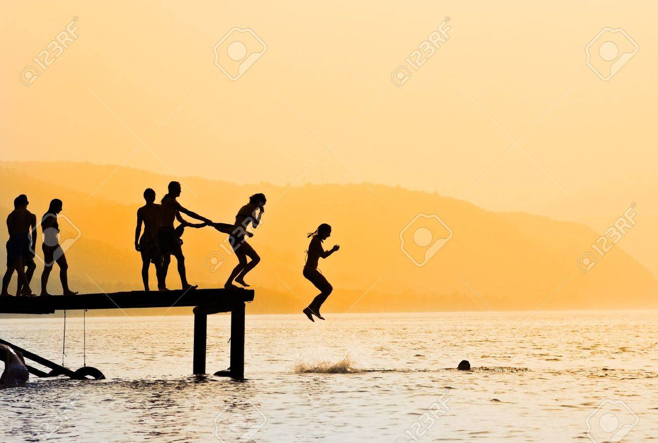 Silhouettes of kids who jump off dock on the lake at sunset. Stock Photo - 10477947
