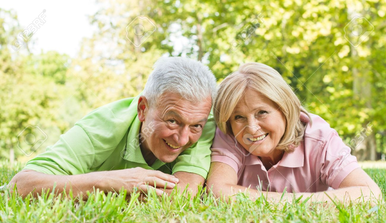 Portrait of happy old people lying on green grass. - 10760292