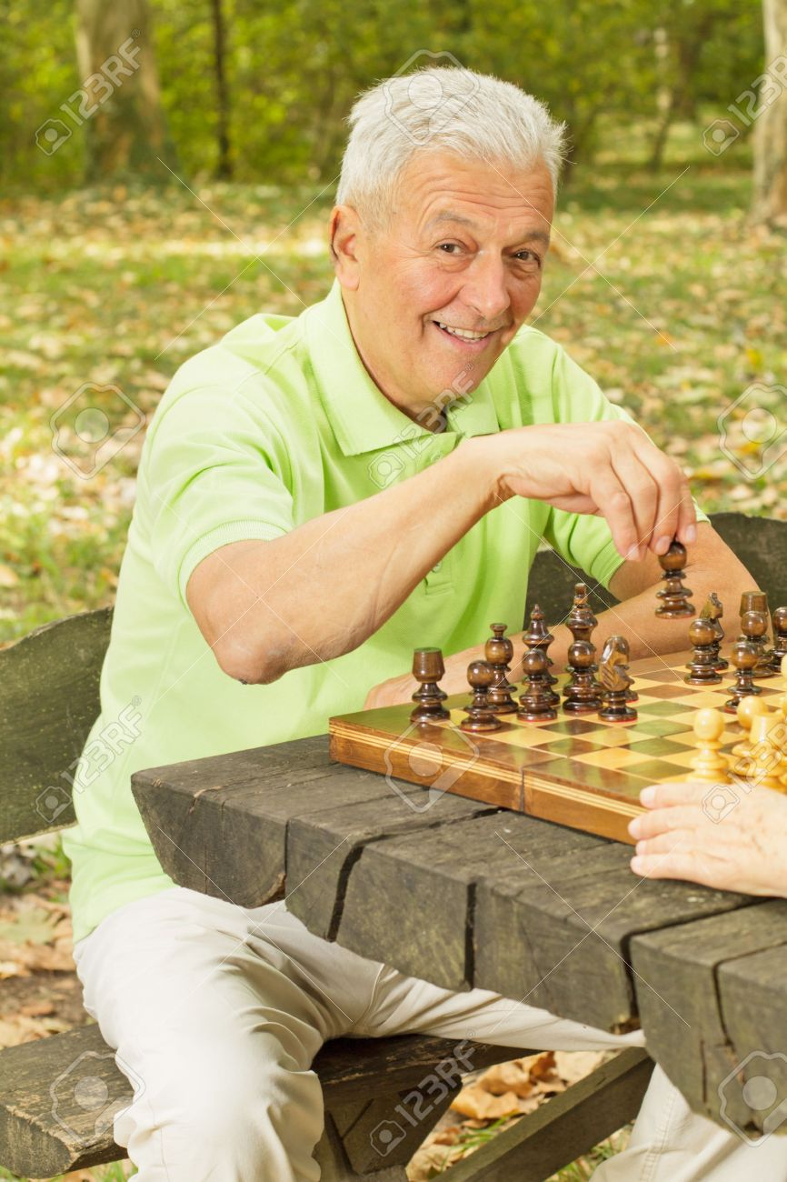 Elderly man playing chess in the park. - 10760304