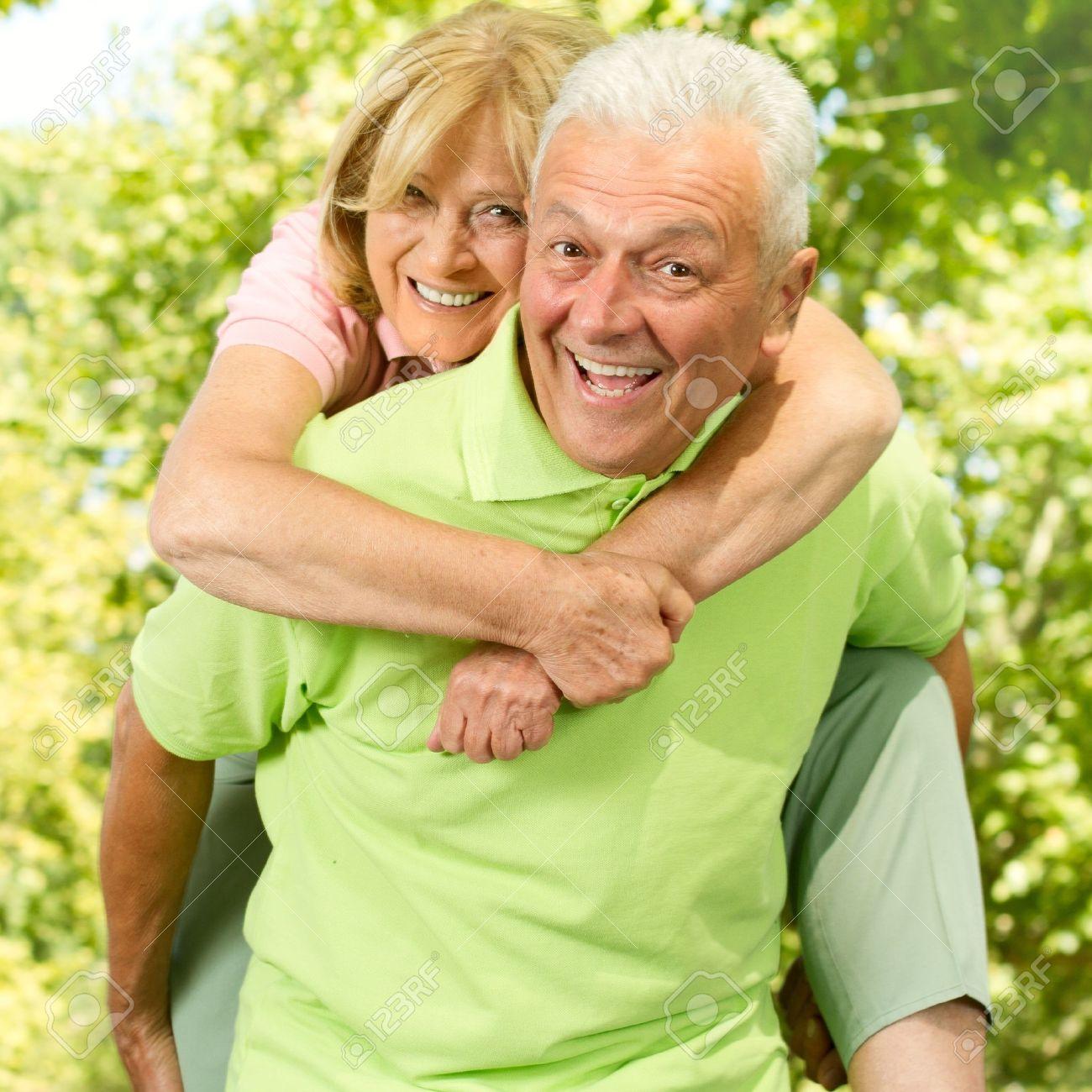 Portrait of happy senior man giving piggyback ride outdoors. - 10760283