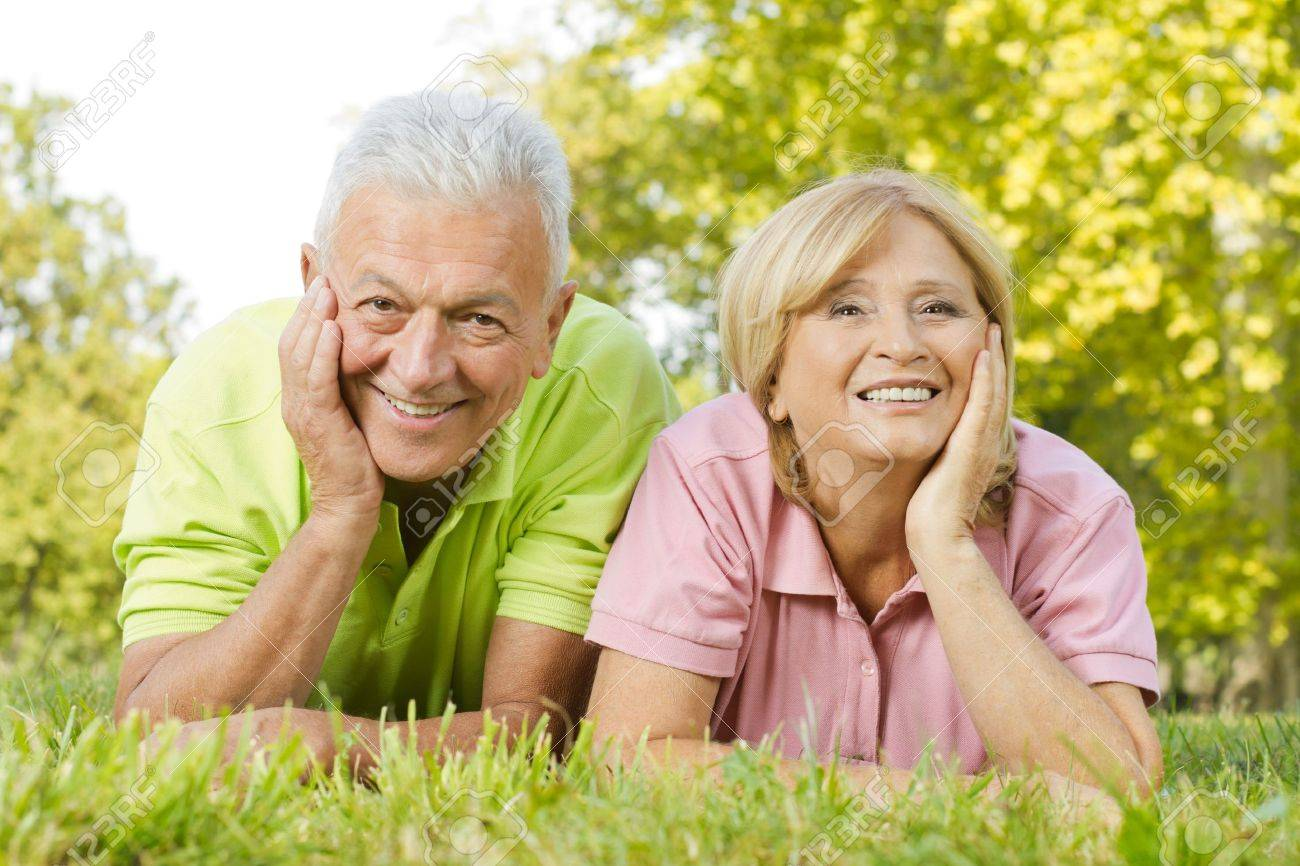 Portrait of happy old people lying on green grass. Stock Photo - 11212463