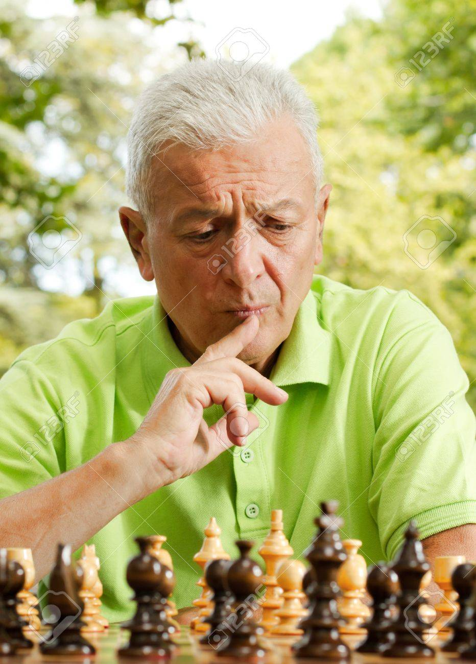 Portrait of worried elderly man playing chess outdoors. - 11212457