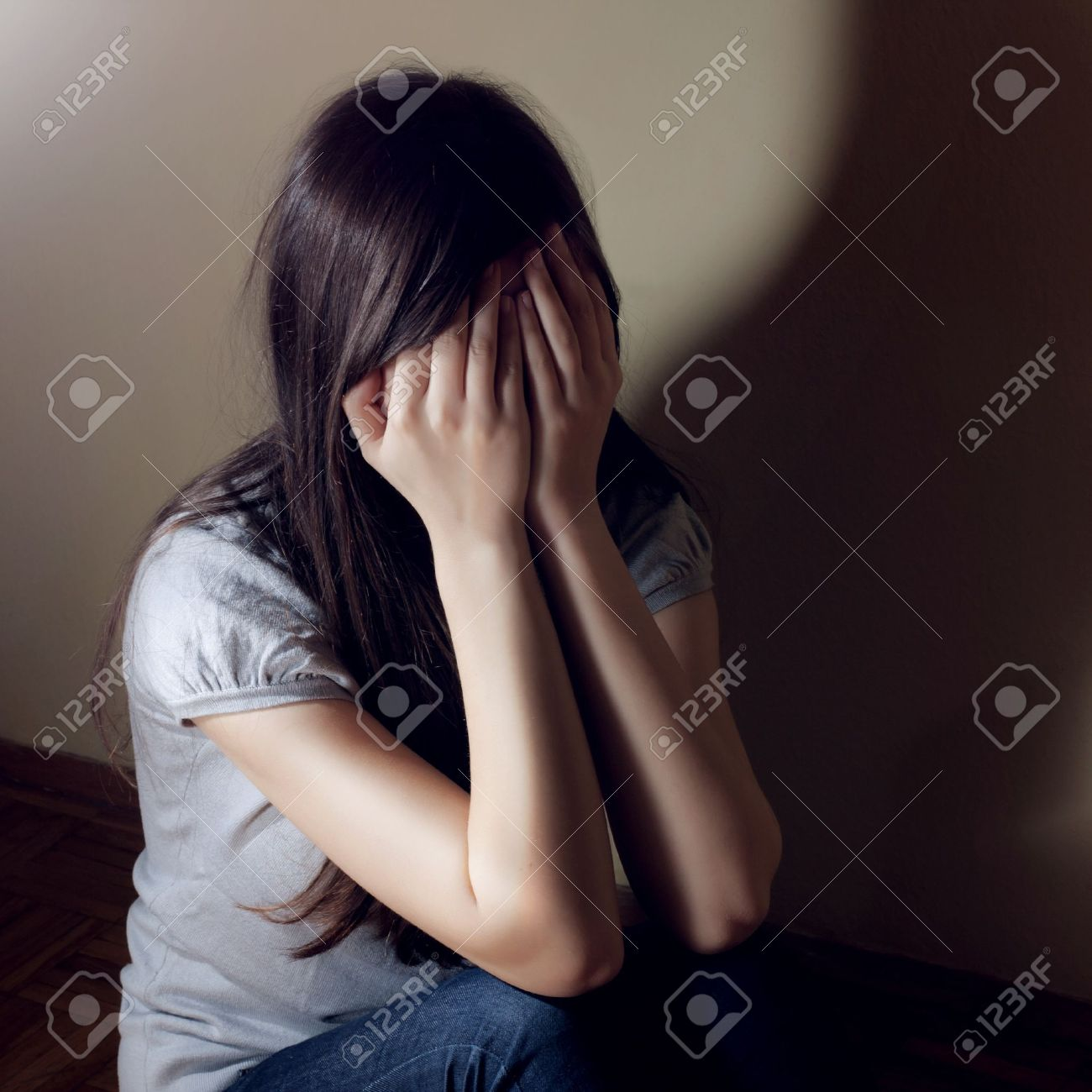 Depressed teenage girl cover her face with hand. - 12323069