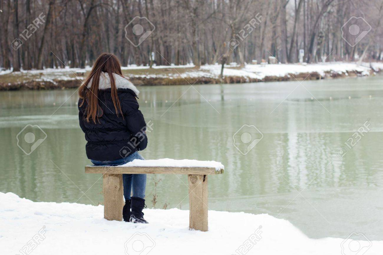 A lonely young woman sitting on a bench beside the lake, winter time. - 12323166