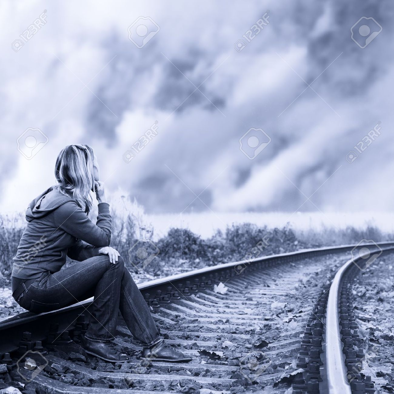 Lonely woman sitting on the rails and thinking - 13546273