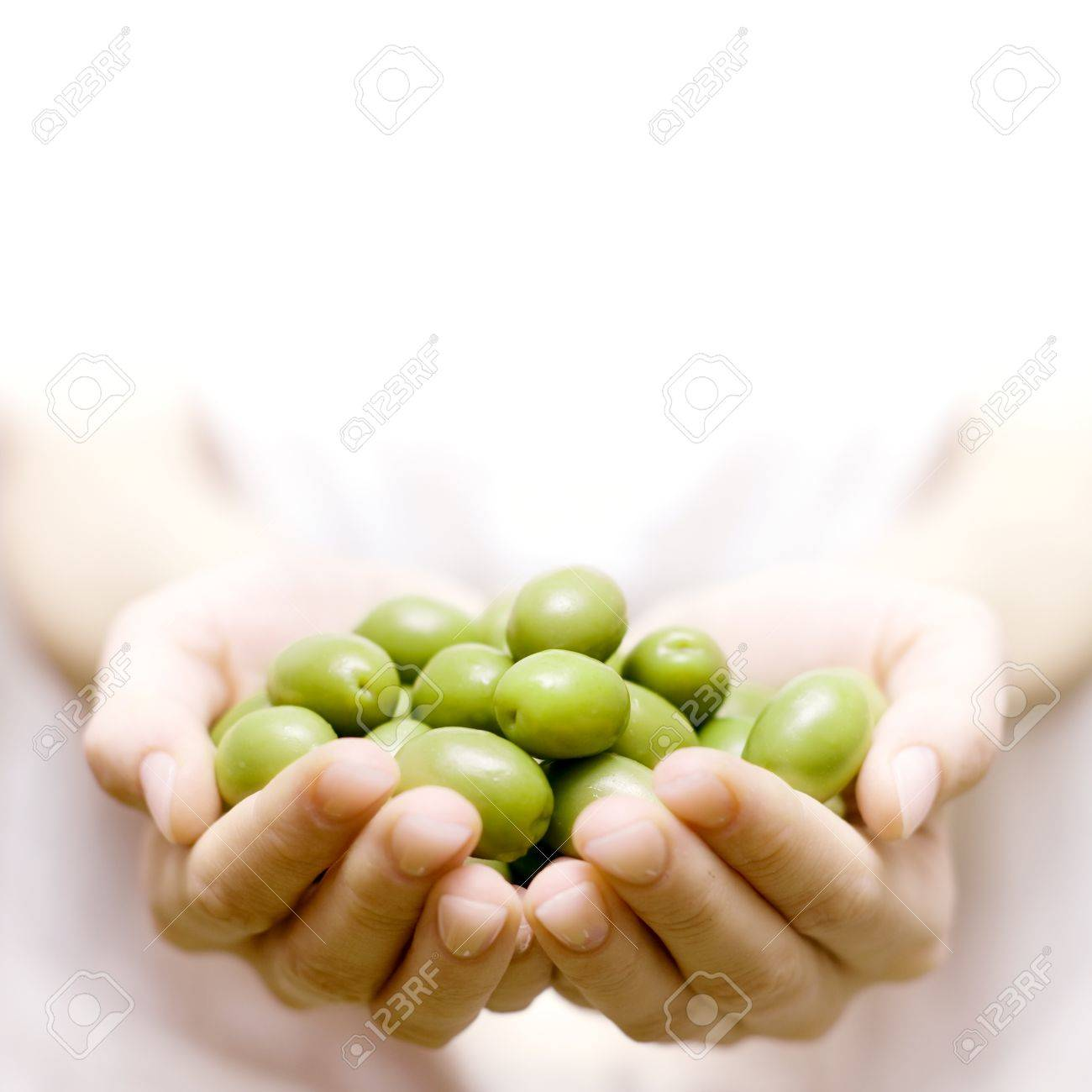 Human hands holding green olive with space for text - 13548534