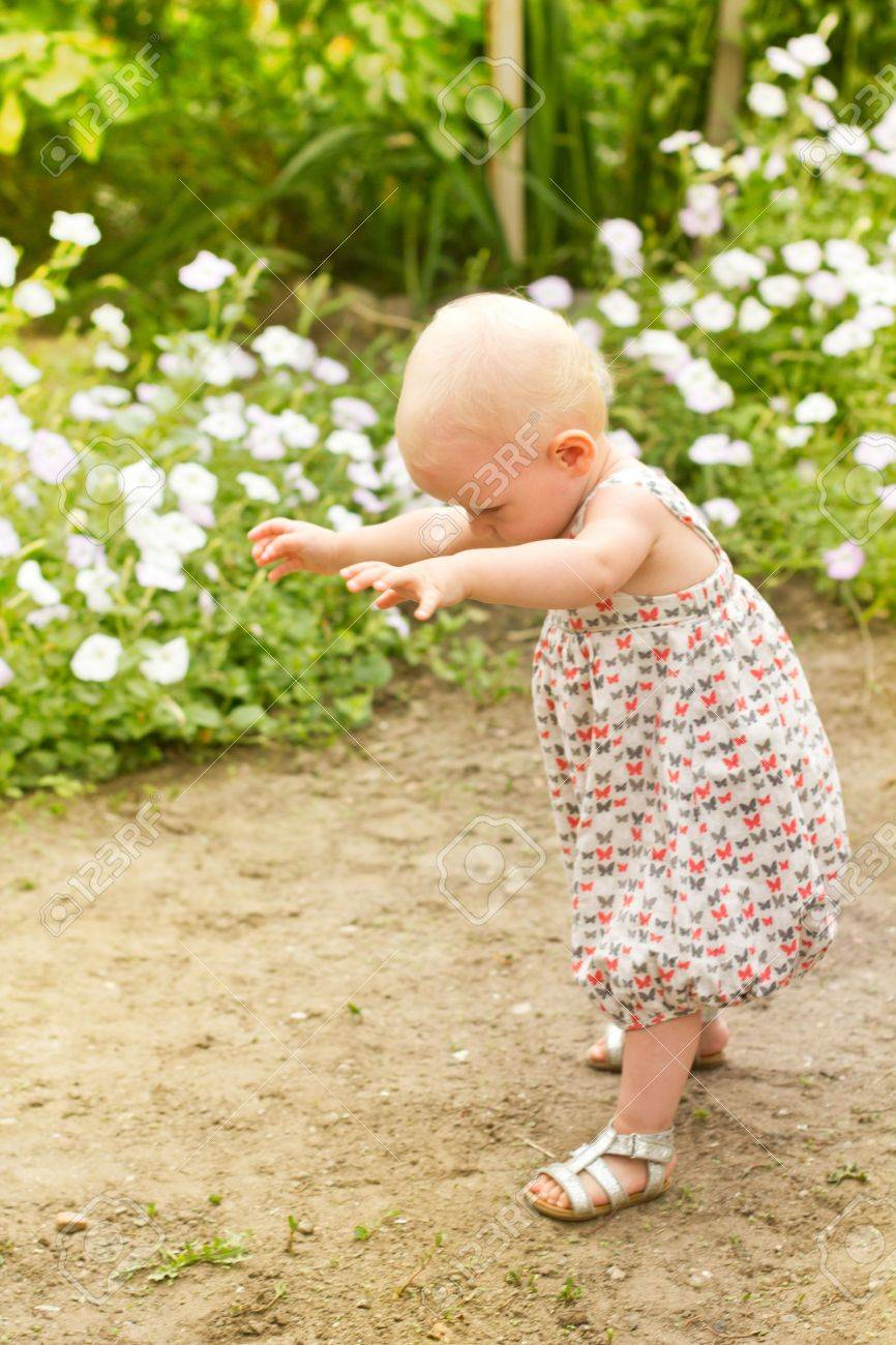 Baby girl,one year old ,making her first step in the park - 14959152