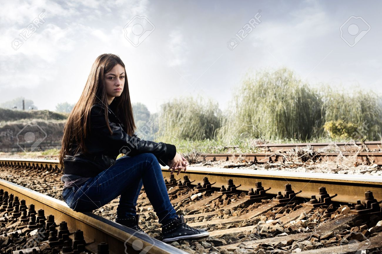 Lonely teenage girl sitting on railroad and thinking. - 15782127