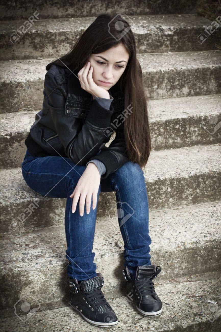 Portrait of depressed teenage girl sitting on staircase. - 15782160