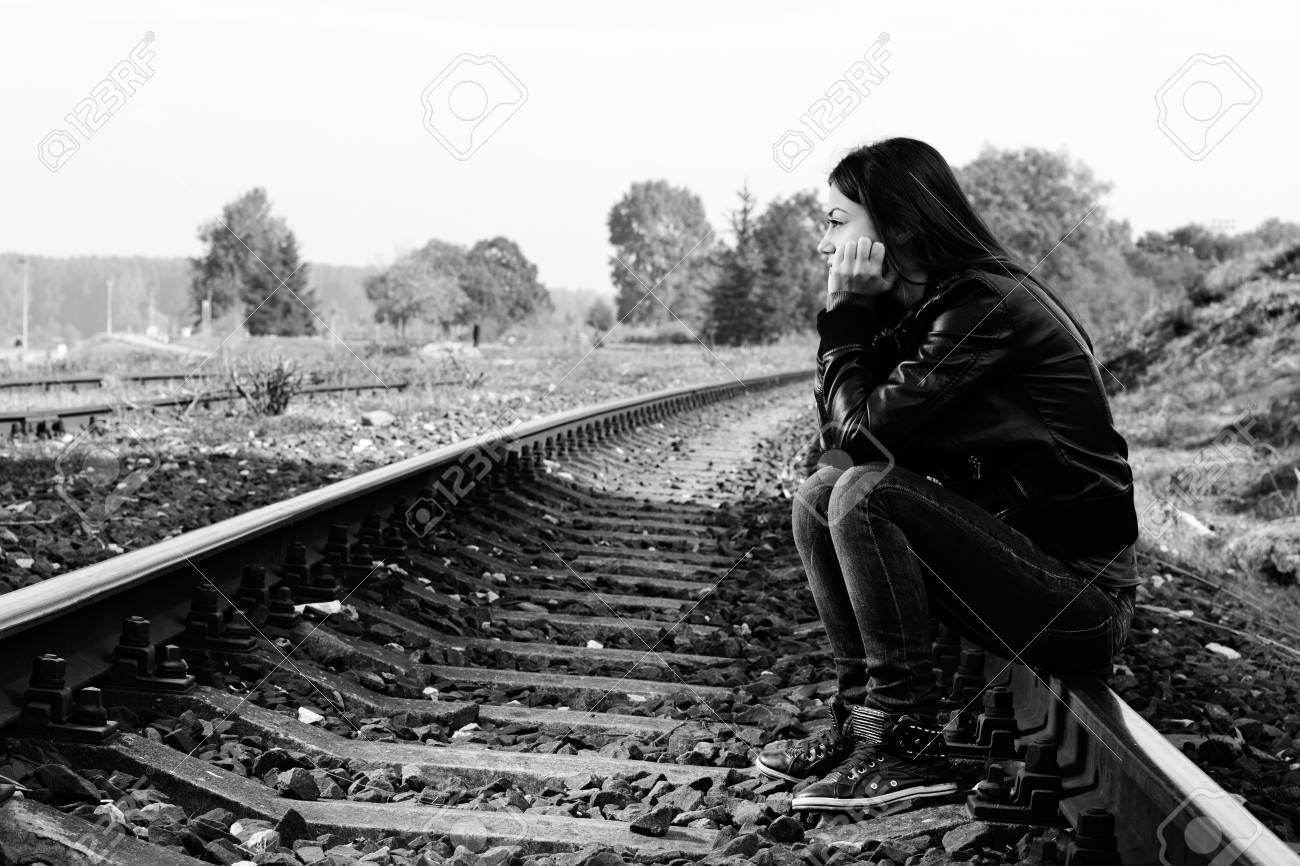Depressed and lonely teenage girl with hands over her face sitting on the railroad - 16126626