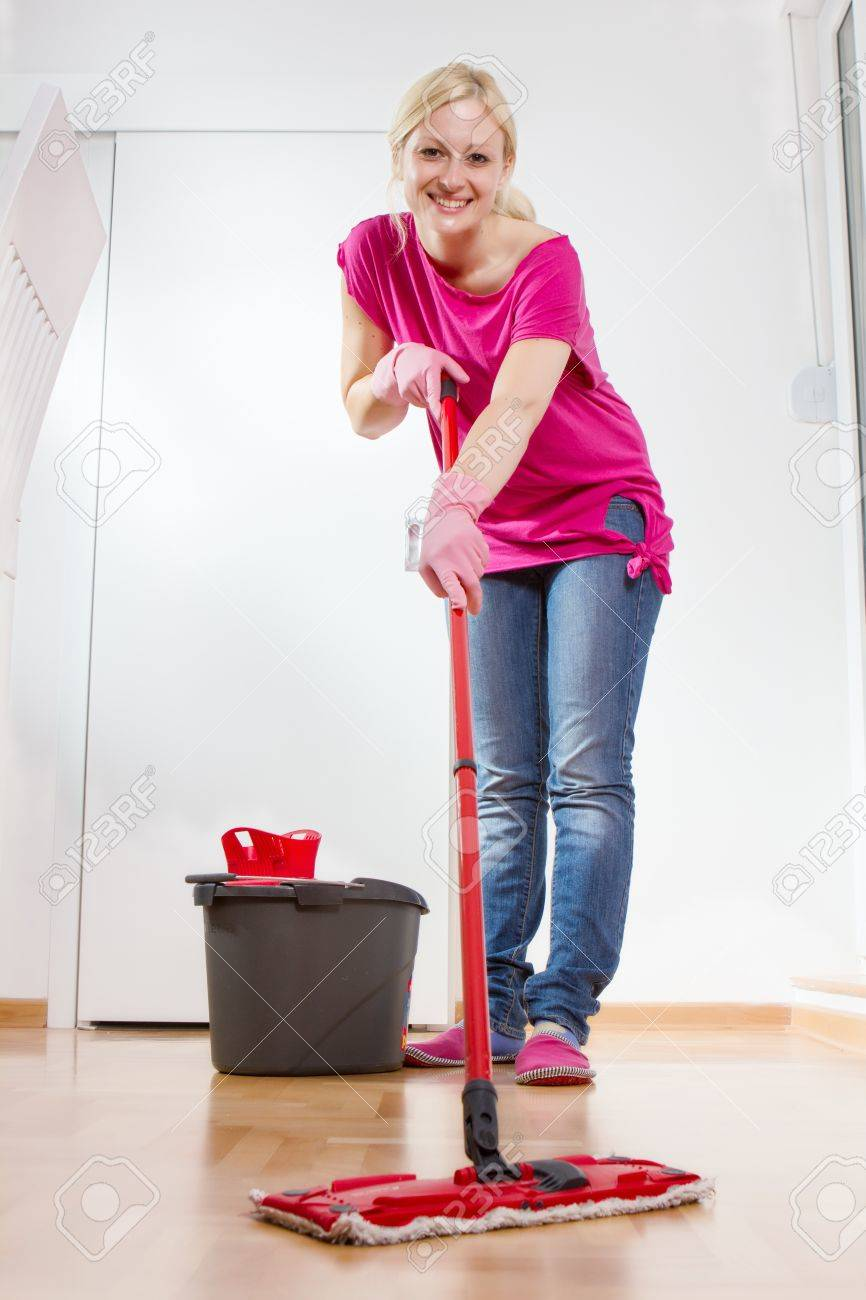 Young woman cleaning and mopping floor at home. - 20467398