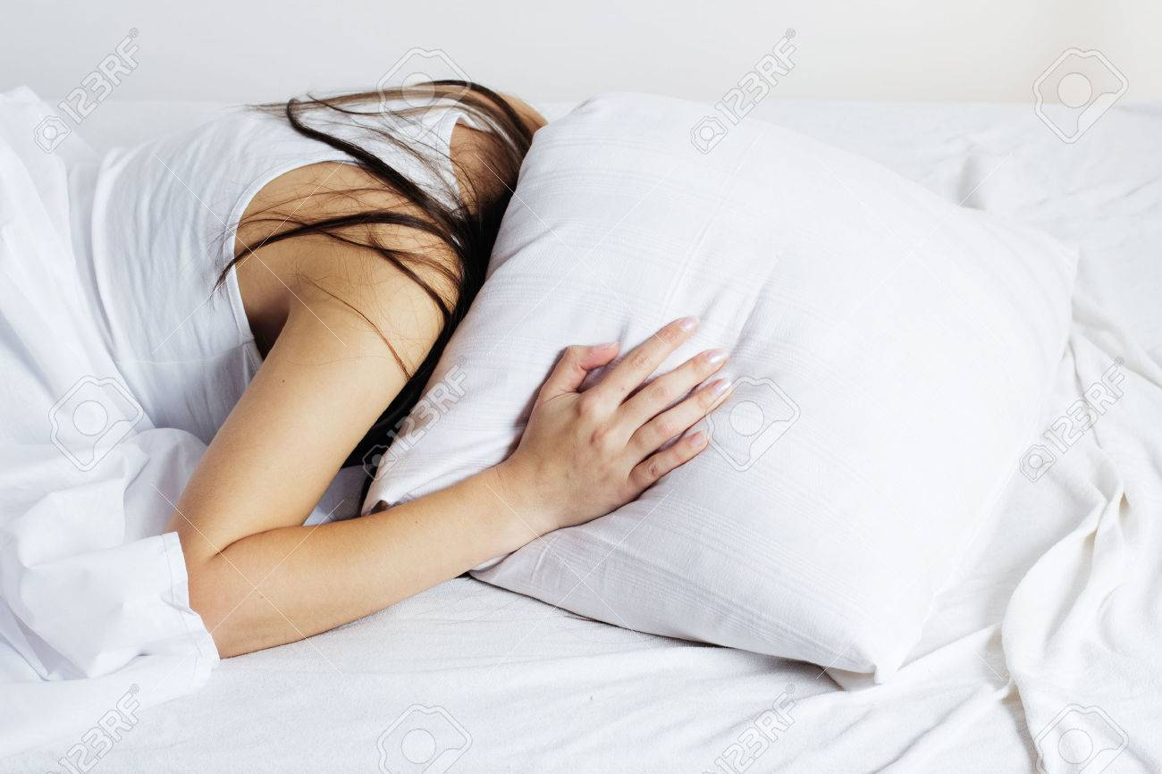 Girl covered her head with a pillow.Insomnia - 24297173