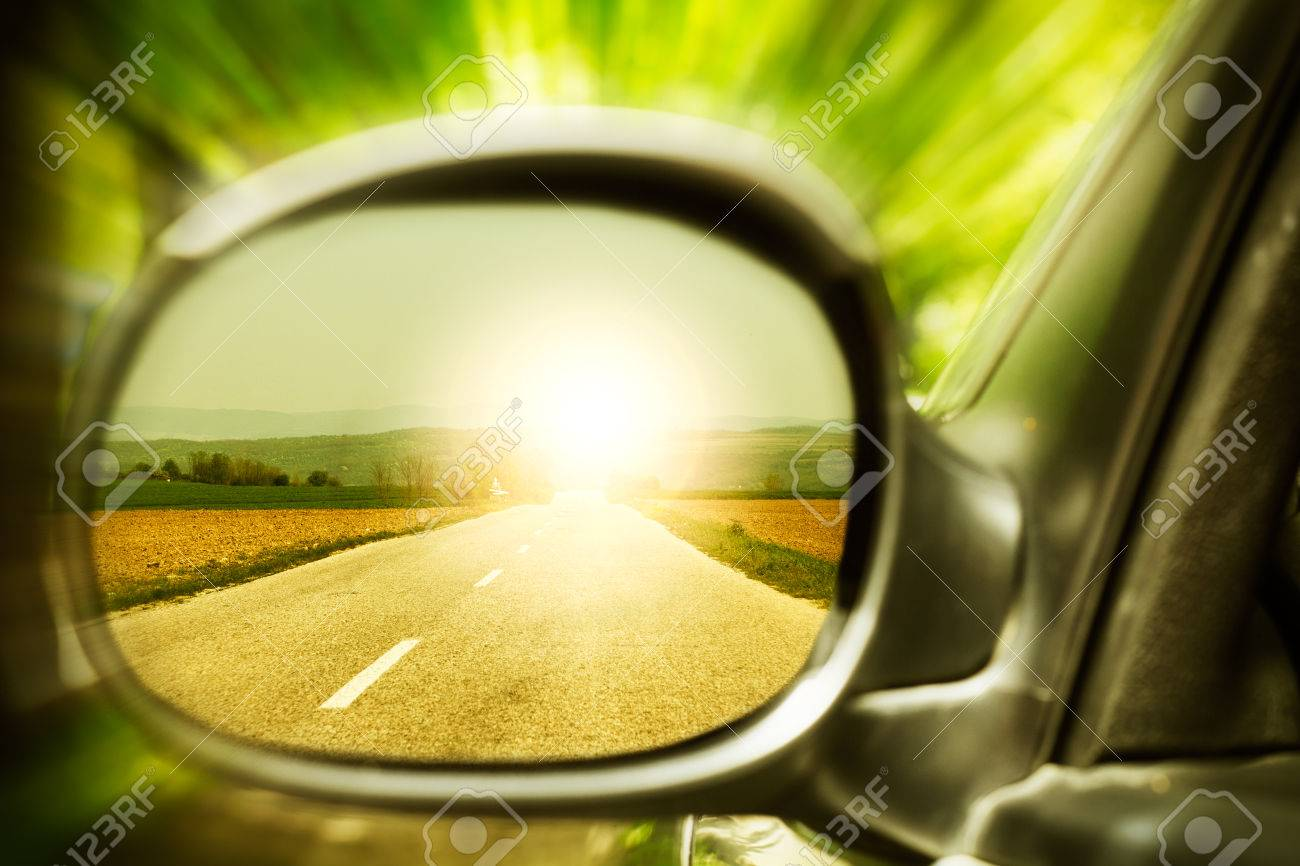 Sunset on a lonely country road, as seen in car mirror - 24540449
