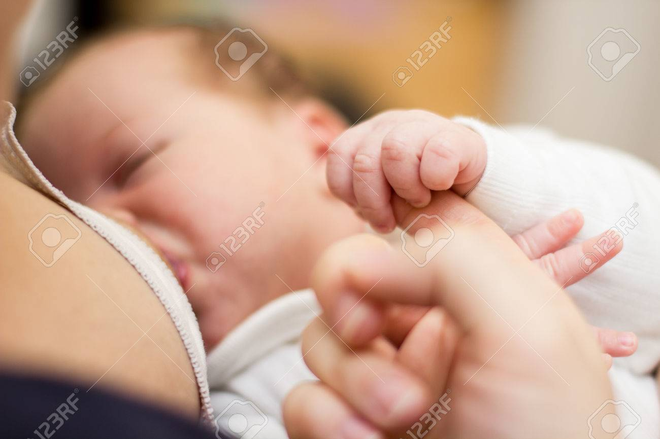 Newborn baby holding mother finger and breastfeeding - 26961795