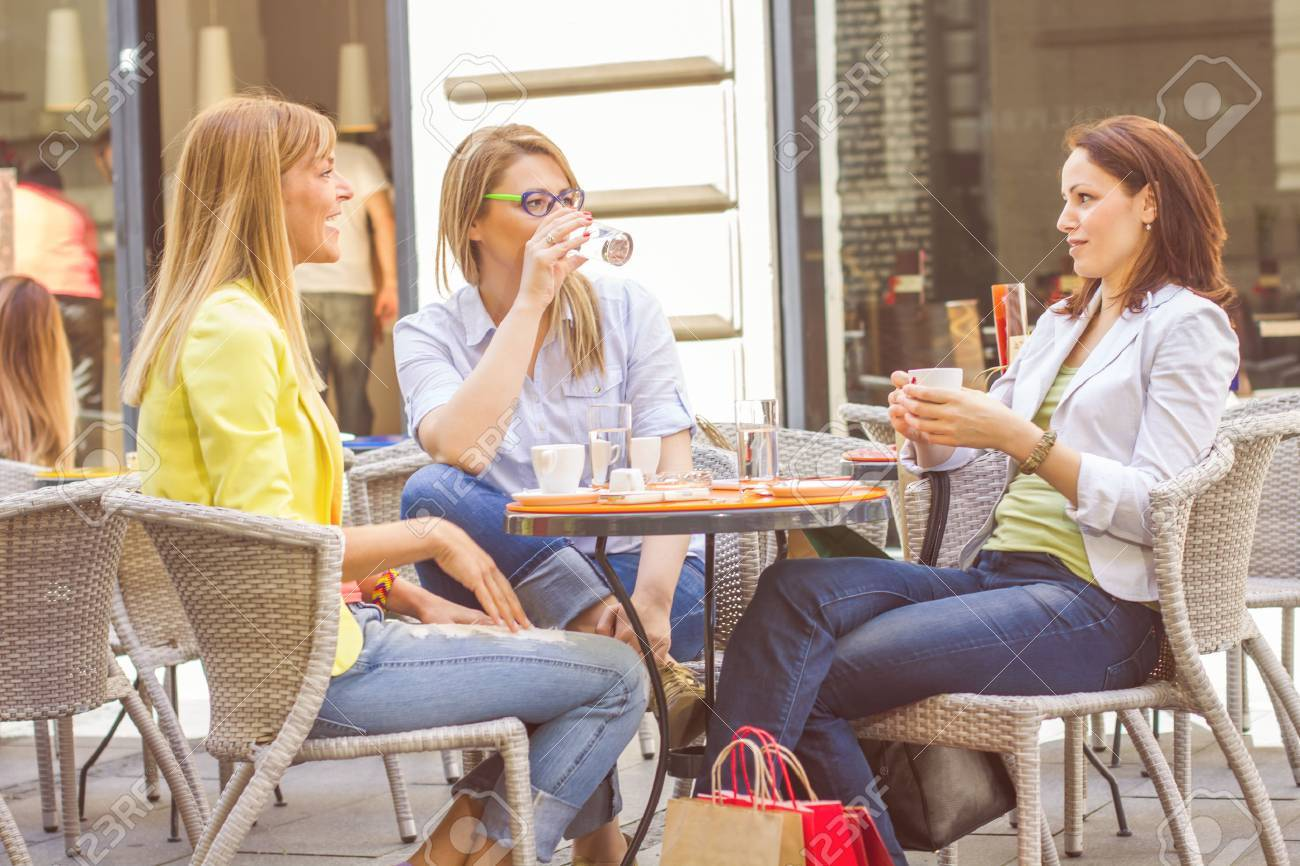 Three Young Women have Coffee Break Together in street cafe. Caucasian female relaxing on beautiful summer day in the city. - 40819536