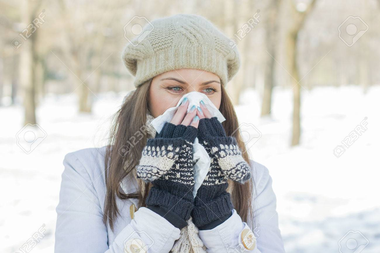 Young Woman in Winter Clothing Blowing Nose with tissue paper outdoor - 43474207