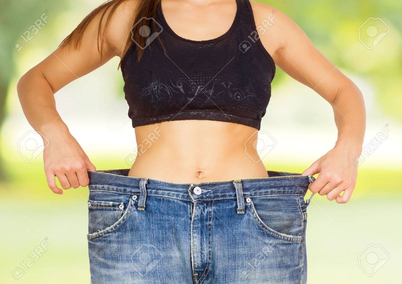 Slim Waist of Young Woman with perfect healthy thin body,showing her old jeans after successful diet over nature background. - 46977314
