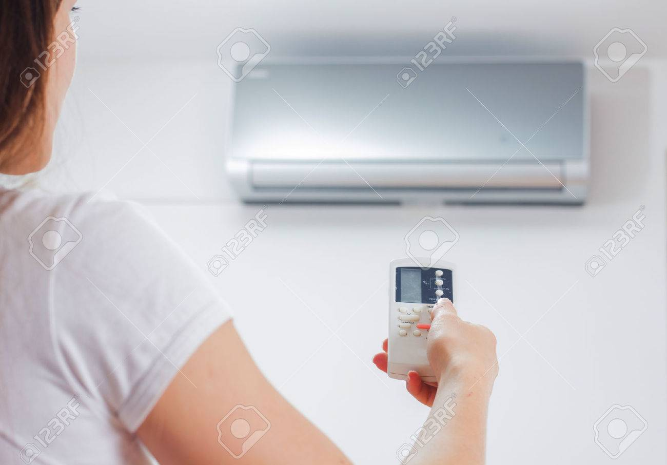 Air Conditioner , woman hand with remote control, adjustment temperature,at home - 50879293