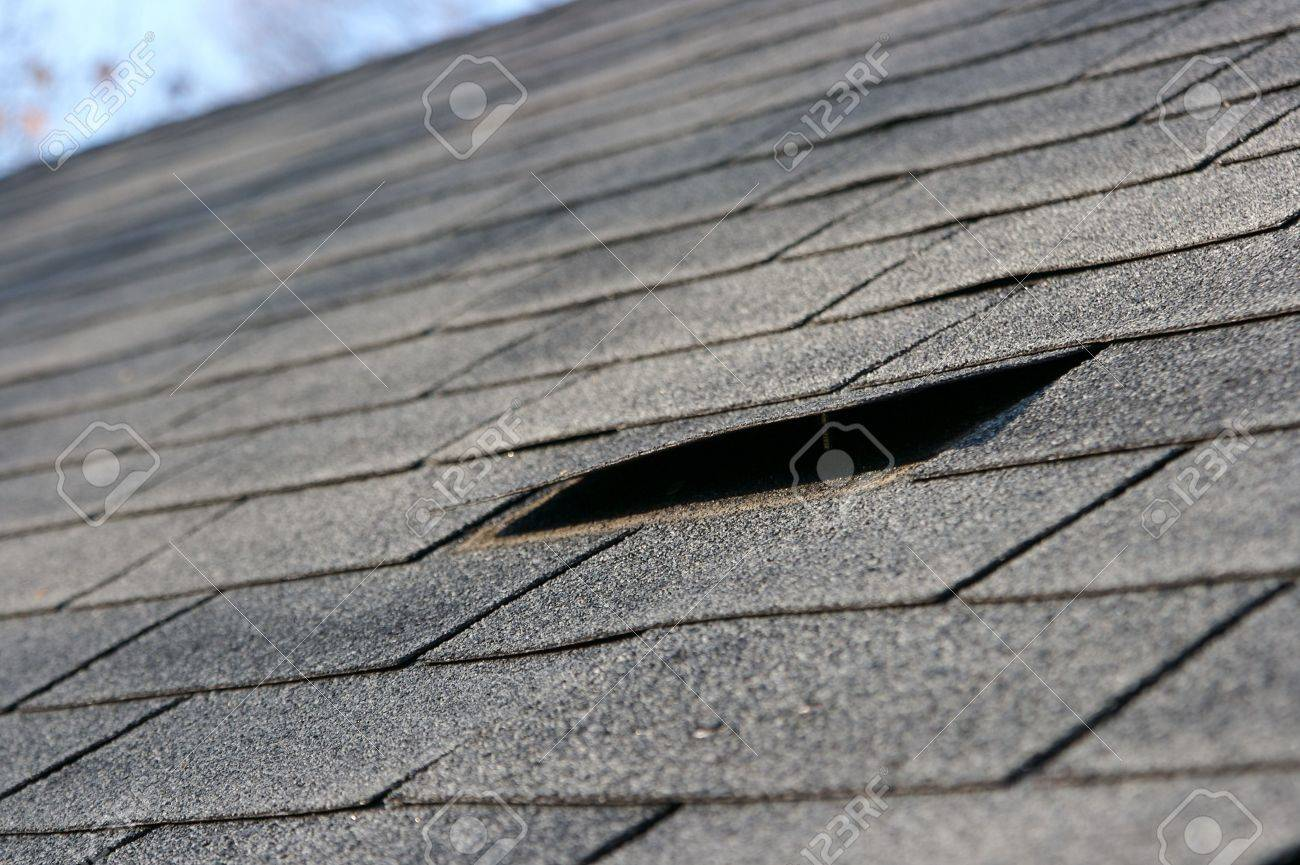 Roofing trouble - damage to shingles that needs repair - home maintenance series. Narrow DOF Stock Photo - 1941850
