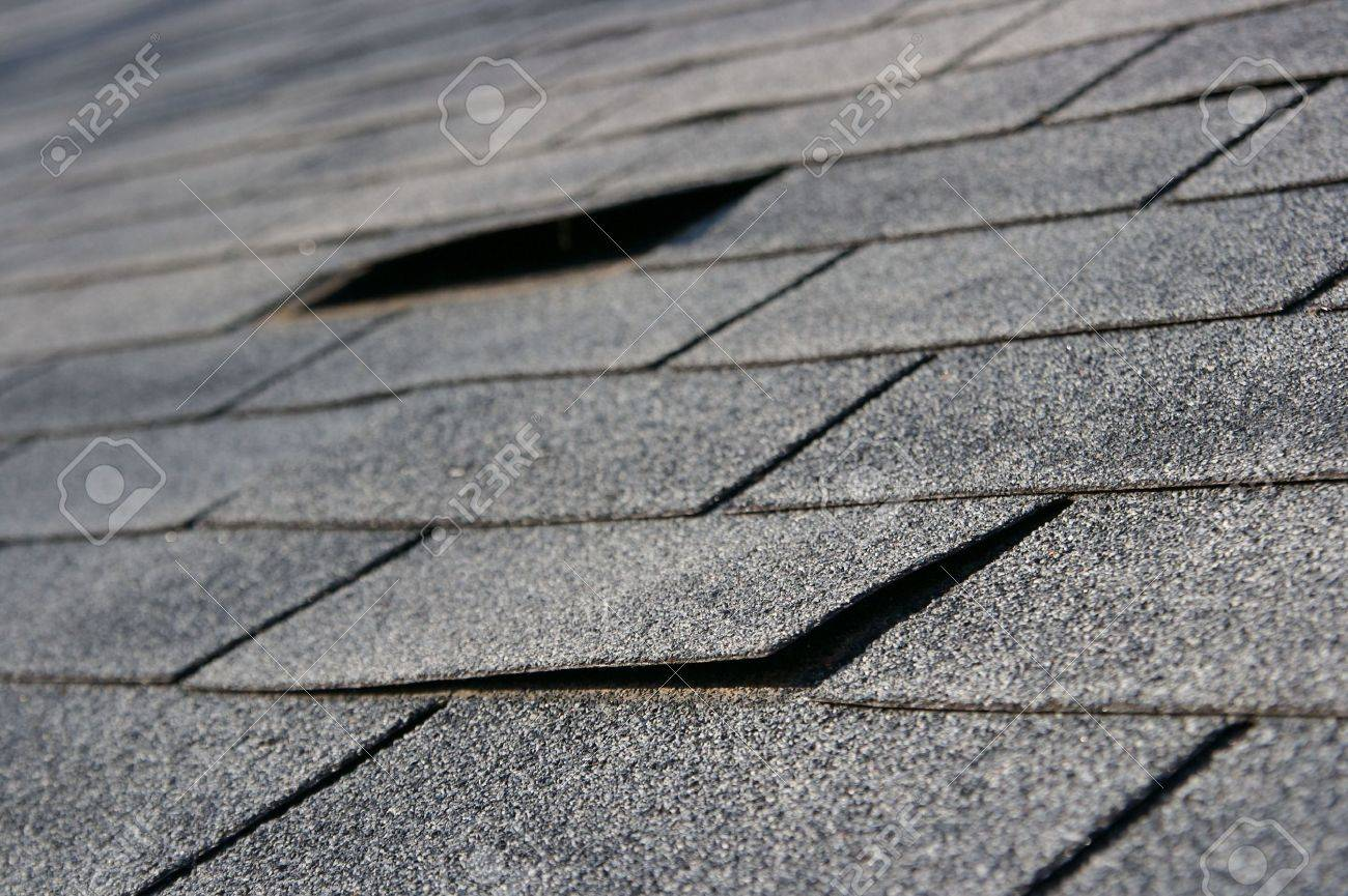Roofing trouble - damage to shingles that needs repair - home maintenance series. Narrow DOF Stock Photo - 1941853