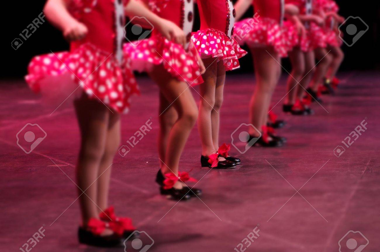 Performing on stage, a group of young dancers show off their talent and bright costumes - image highlights a narrow depth of field on the girl in the middle of the line Stock Photo - 2934417