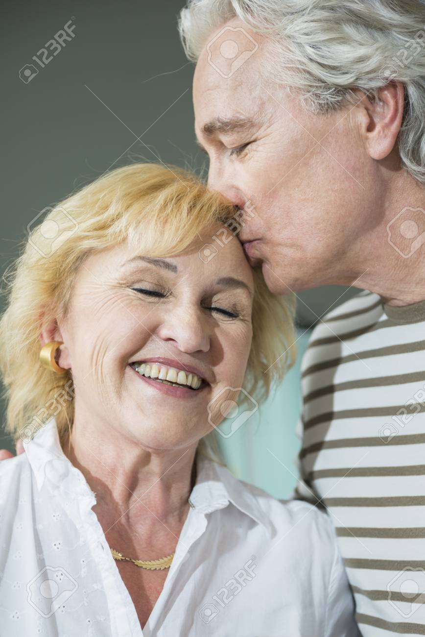 mature man kissing mature woman on forehead, smiling stock photo