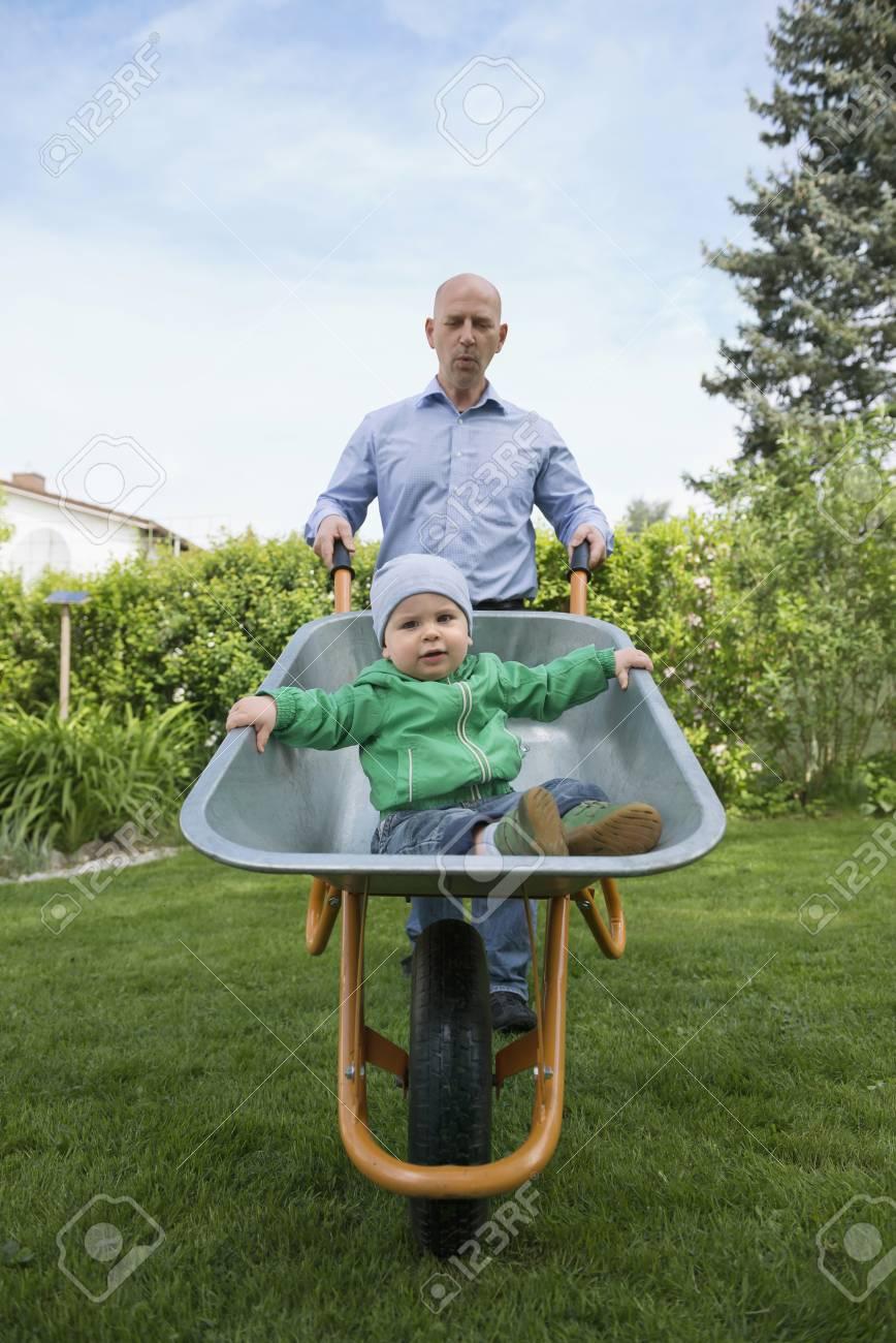 Father Pushing Baby Son In Wheelbarrow Garden
