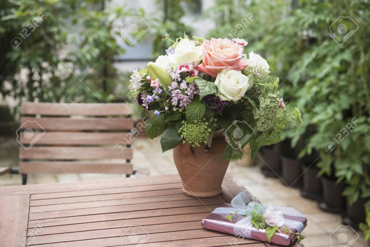 Cadeau met boeket bloemen op tafel in tuin münchen beieren