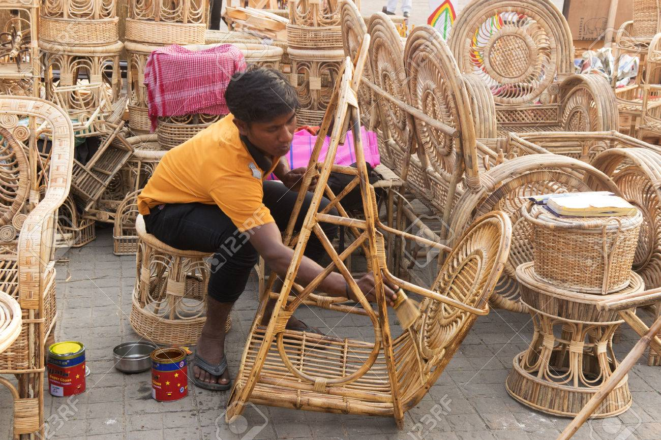 Stock photo unidentified person polishing cane furniture handicrafts on display