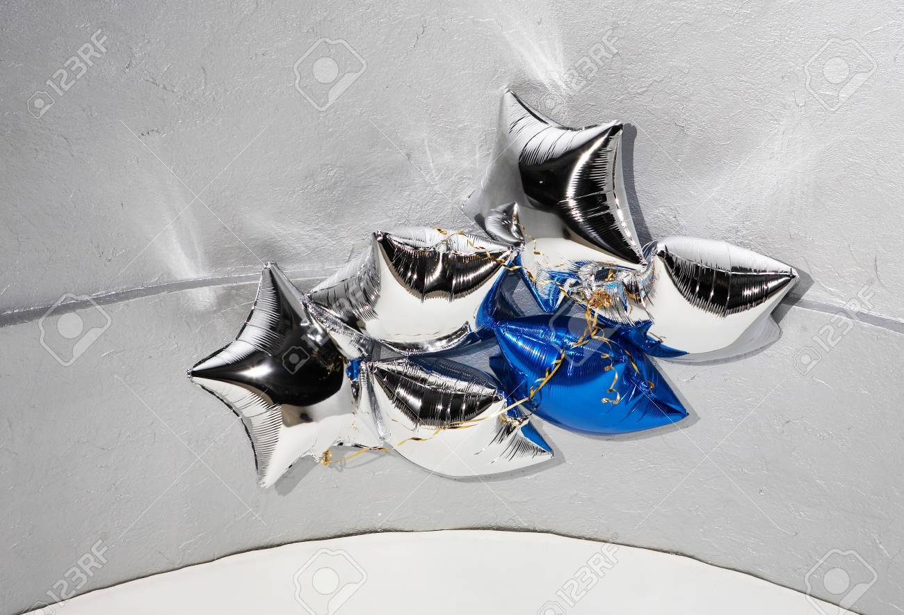Six star silver and blue balloons with golden ribbons under ceiling Stock Photo - 4159293
