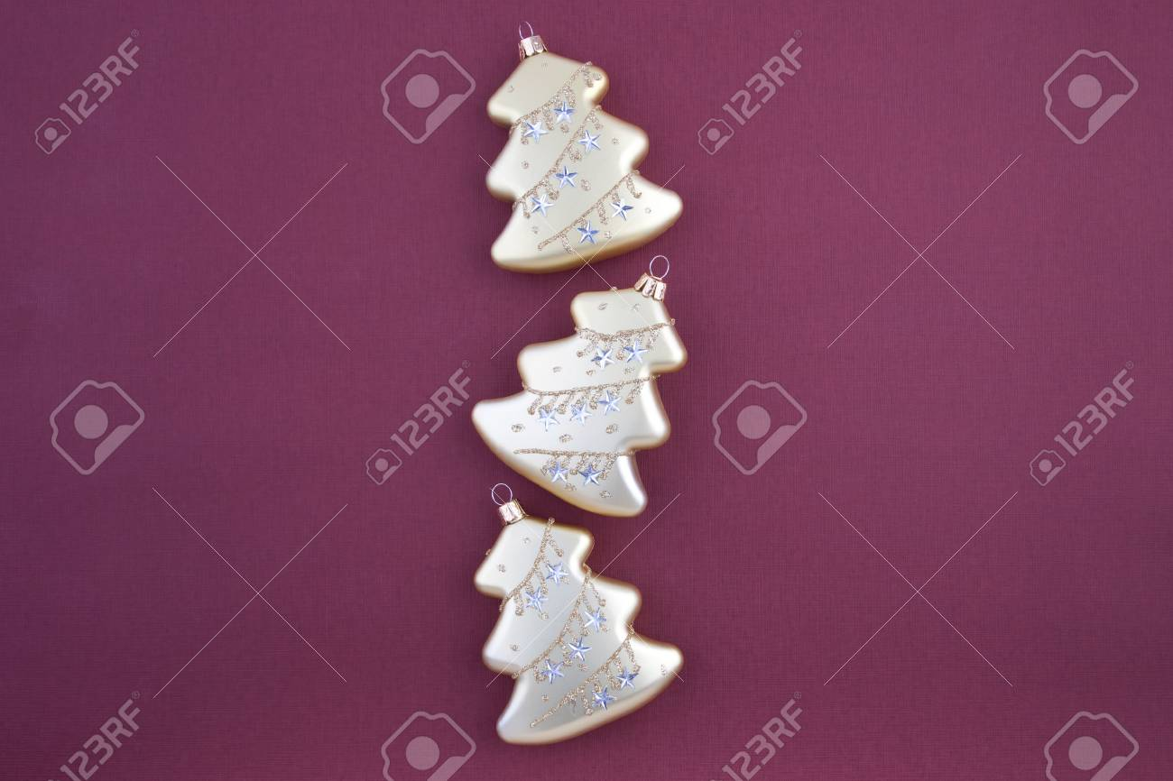 Three Christmas decoration gold firs on vinous textured paper background Stock Photo - 5950935
