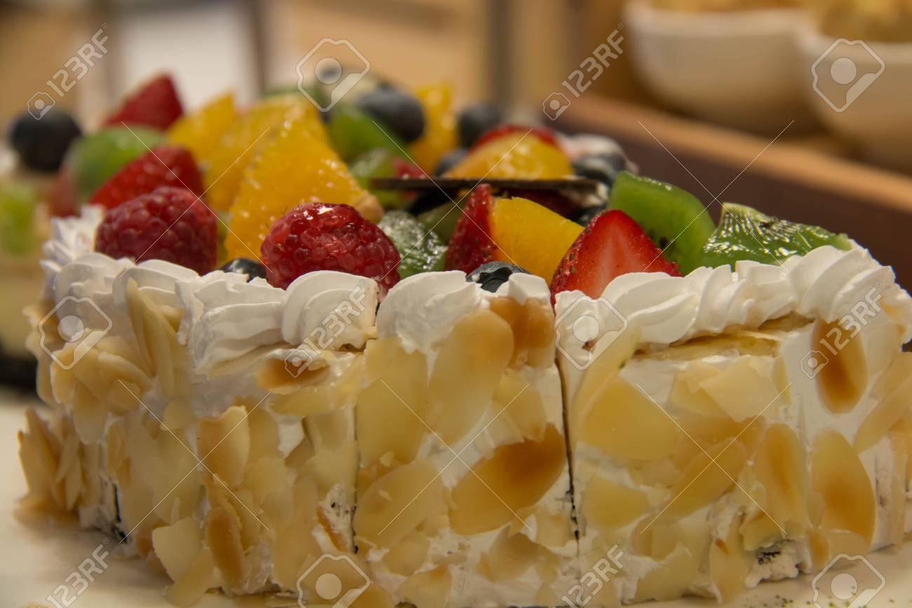 A Cuted Fruit Birthday Cake With Mixedfruit On It Standard Bild