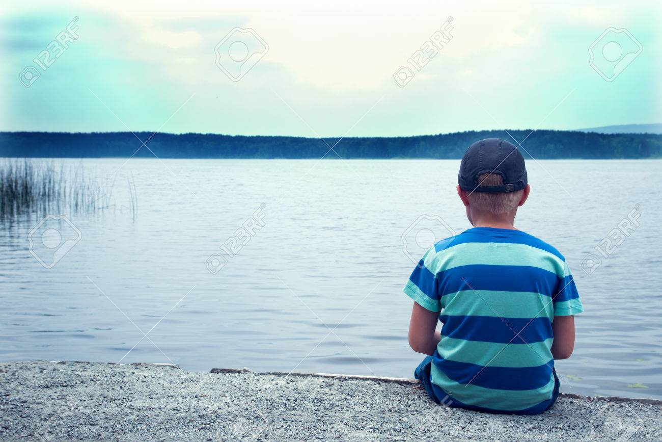 Sad child sitting alone at the lake on a cloudy day back view stock photo