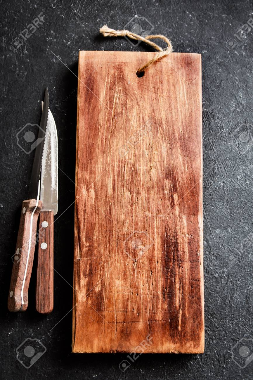 Rustic Wooden Cutting Board And Knives On Black Stone Background Stock Photo Picture And Royalty Free Image Image 75504823