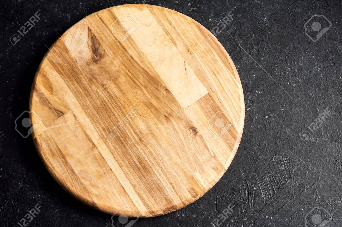 Rustic Wooden Round Cutting Board On Black Stone Background Close Stock Photo Picture And Royalty Free Image Image 81427616