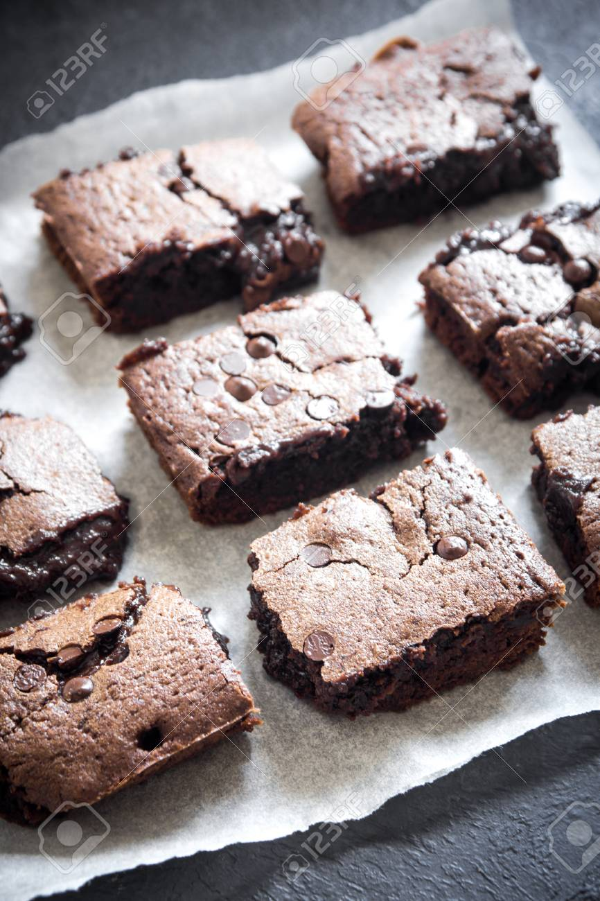 Double Chocolate Brownies. Homemade chocolate fudge brownies with chocolate chips on baking paper and black
