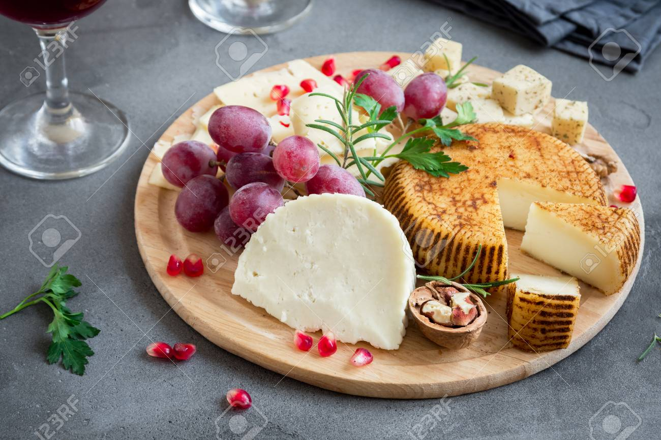 Cheese Platter With Assorted Cheeses Grapes Nuts Over Gray Stock Photo Picture And Royalty Free Image Image 94666645
