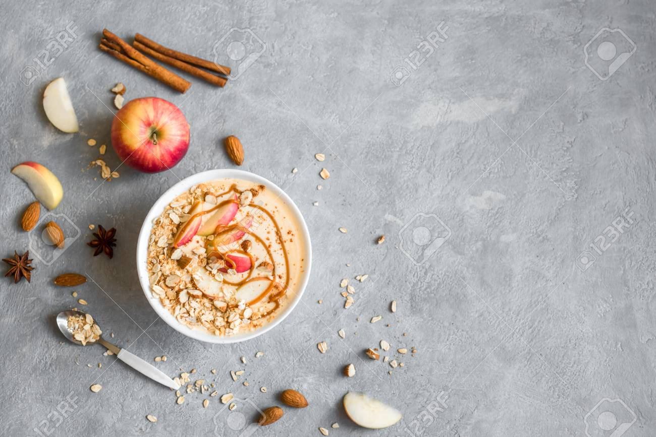 Apple Pie Smoothie Bowl. Breakfast smoothie bowl with apples, cinnamon, almond milk, oat granola, salted caramel and spices, top view, copy space. - 106643775