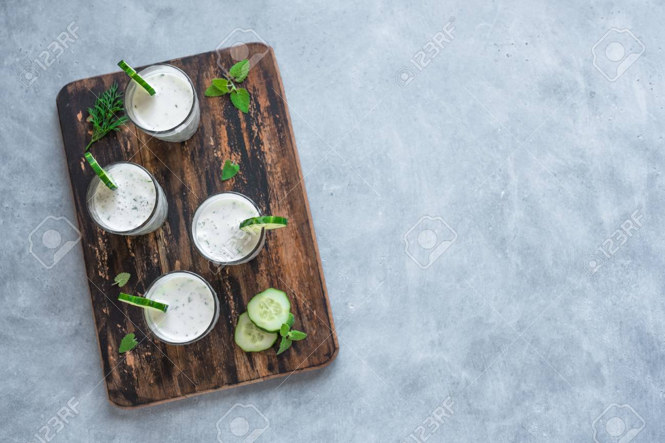 Ayran, homemade yogurt drink (kefir, lassi) with herbs and cucumbers - healthy summer refreshing cold drink, top view, copy space. - 123140447