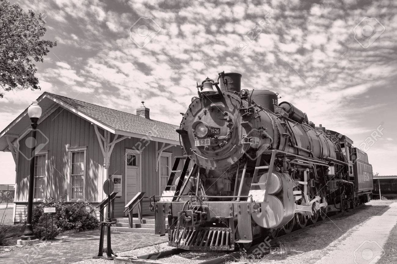 Old railroad steam engine by train station. - 58374422