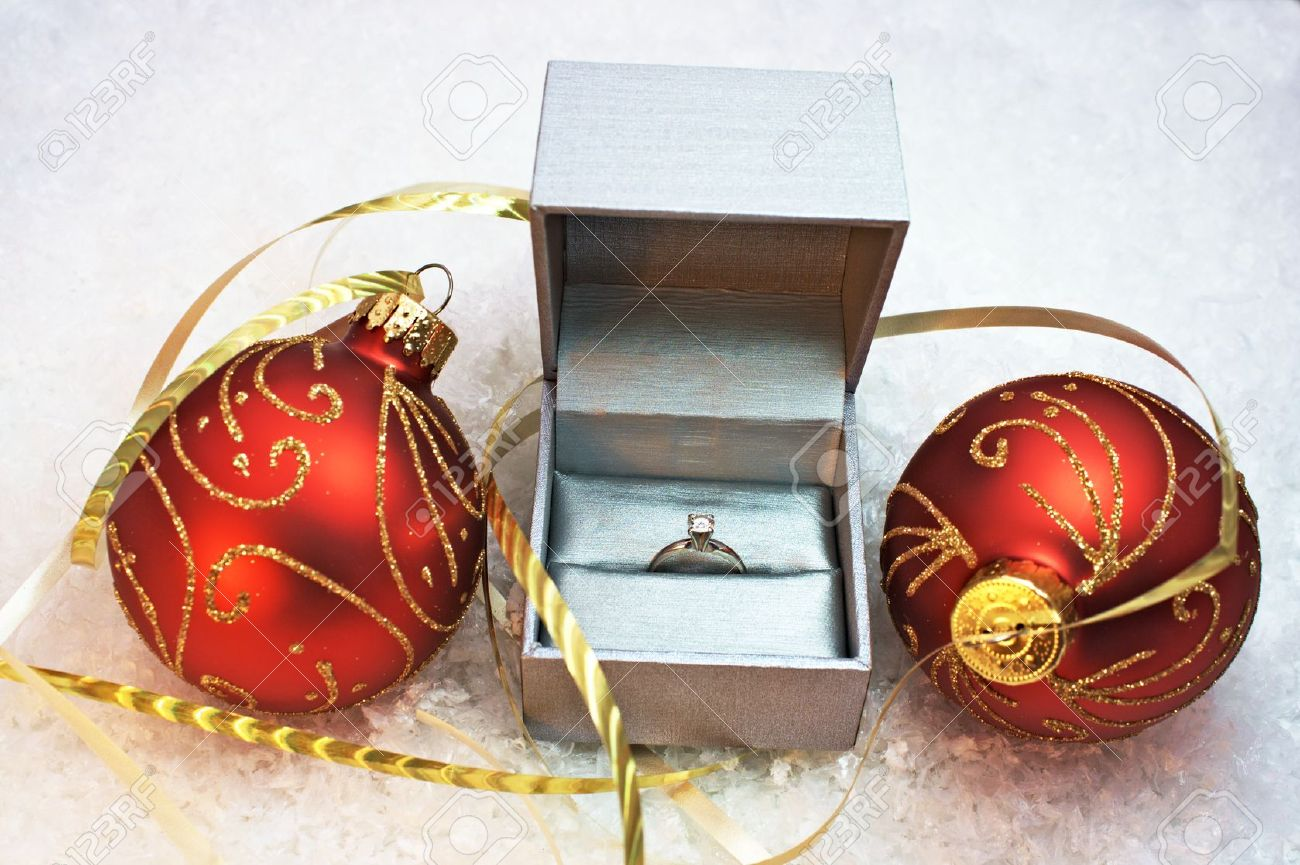 Lovely Engagement Ring In Christmas Ornament Part - 5: Engagement Ring In Silver Box With Two Red And Gold Christmas Ornaments  With Snow Background Stock