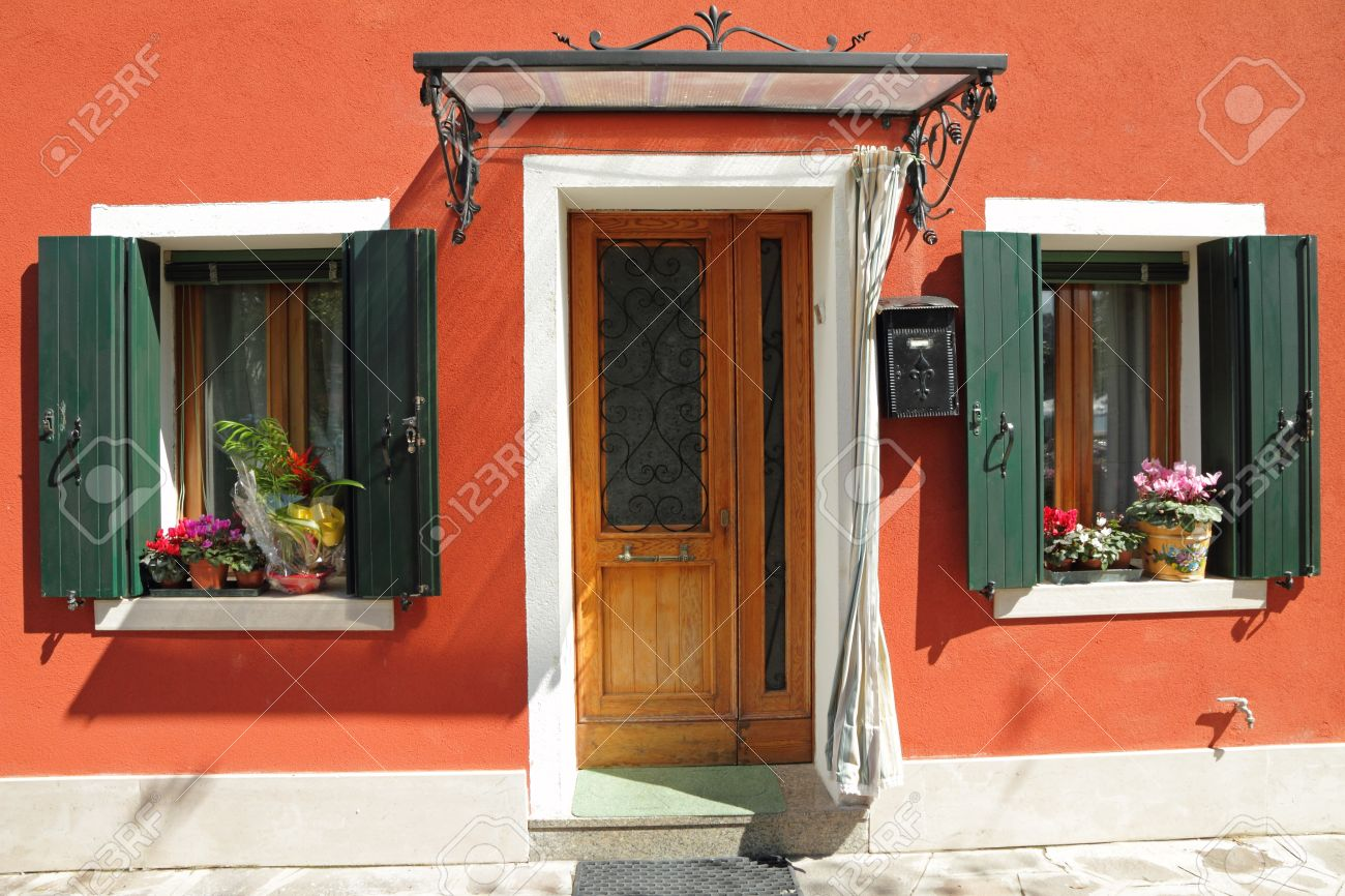 Entrance To The Typical Vivid Painted House With Small Roof Over Door On  Burano Island,