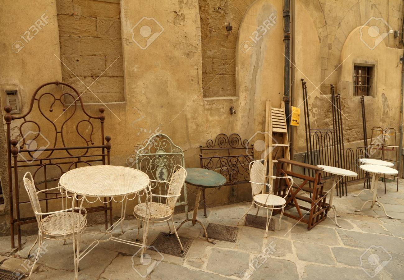 assortment of old fashion furniture objects displayed on street during  famous Antiquity Market in tuscan town - Assortment Of Old Fashion Furniture Objects Displayed On Street