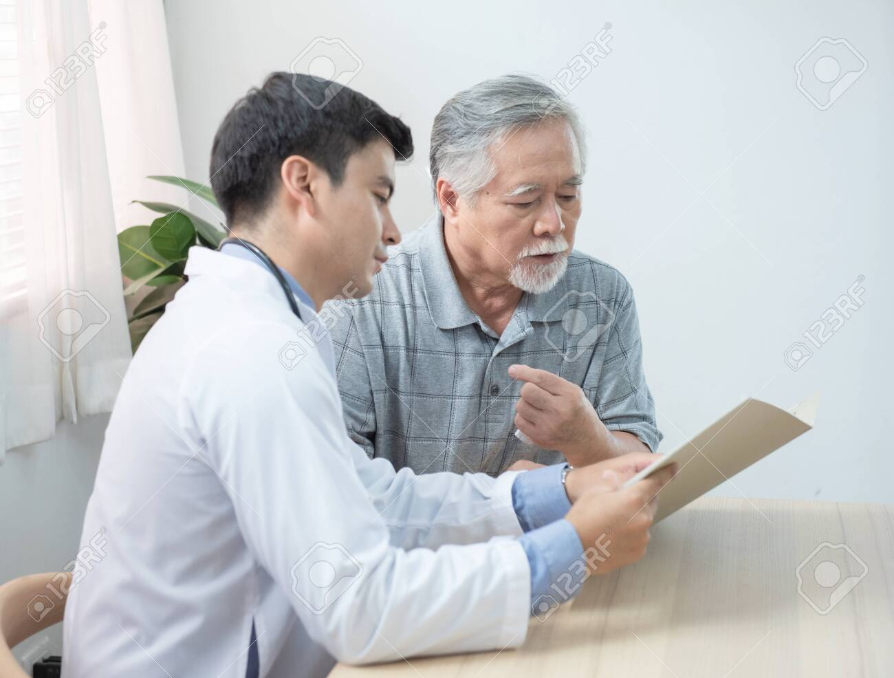 Young caucasian doctor read and explaining consult medical test document for asian elder senior man while visit patient at home.healthcare and medical concept. - 143763636